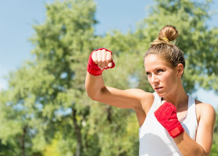 Blonde woman outdoors practicing kickboxing hooks