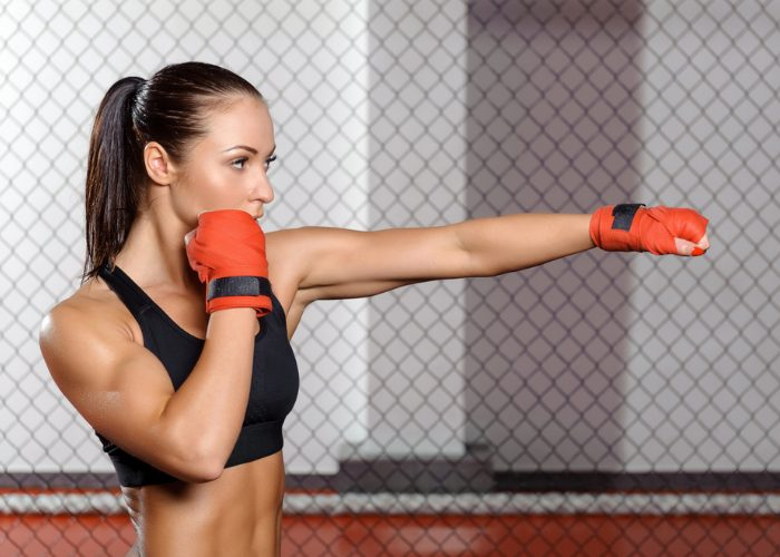 Young fit woman in a kickboxing ring practicing jab punches