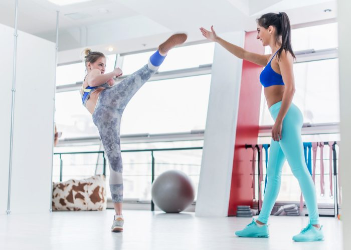 Young woman in a gym practicing kickboxing side kick with an instructor helping her