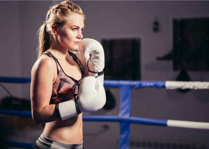Twenty-something year old woman with boxing gloves in her kickboxing stance