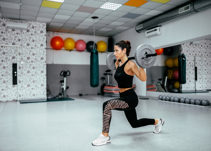 Woman in the middle of a barbell lunge