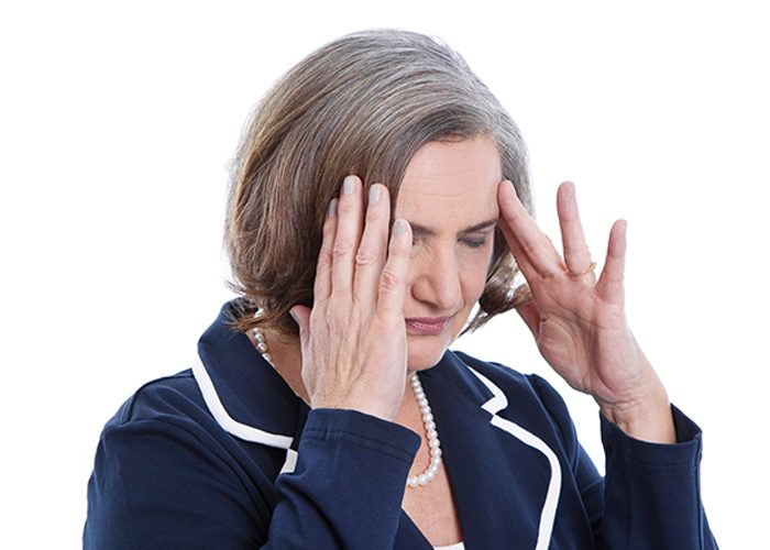 Elderly woman in blue suit jacket with headache touching her temples with both hands