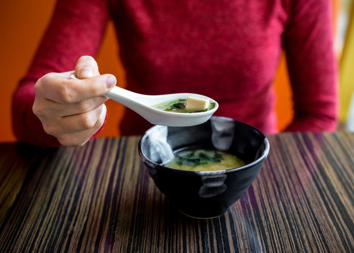 Woman eating a bowl of miso soup at a restaurant