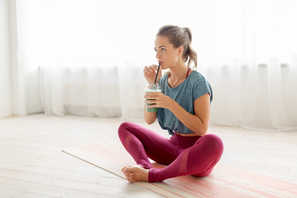 Woman drinking a green pre-workout smoothie before yoga