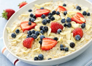 A bowl of oats topped with fruit and nuts prepared for pre-workout purposes