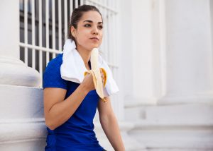 Woman eating a banana as a pre-workout