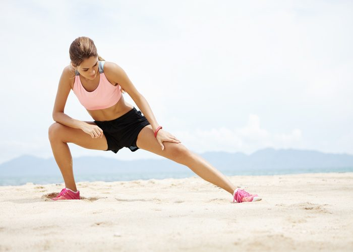 Woman doing a side lunge on the beach