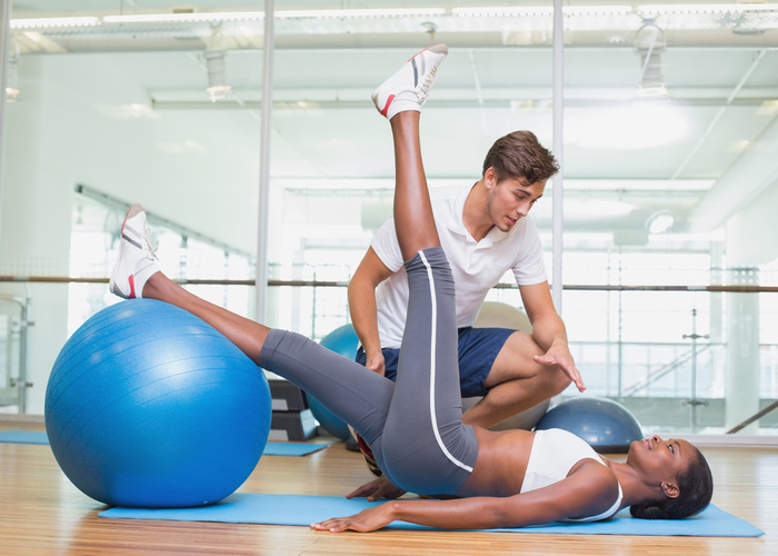 Woman doing stability ball exercises working on legs with her personal trainer in the gym