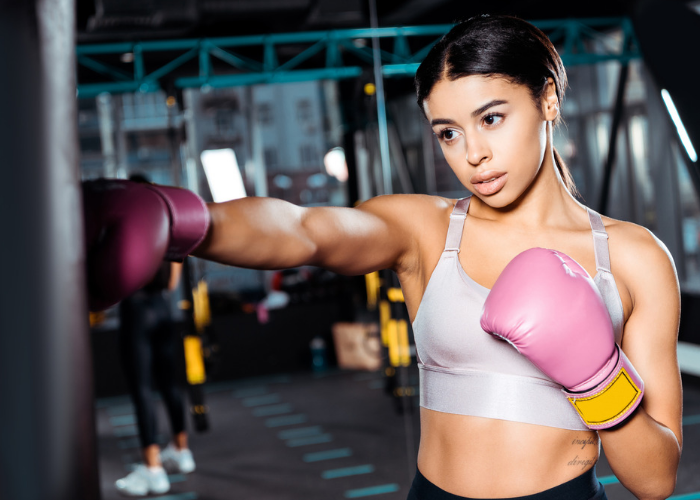 Young woman with pink boxing gloves in a gym practicing american kickboxing