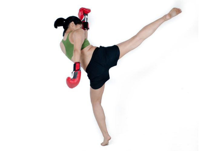 Asian woman with boxing gloves doing high side kick practicing Muay Thai kickboxing