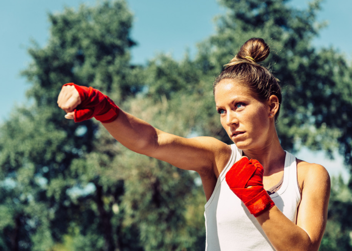 Woman in a park with wrapped fists practicing Tae Bo kickboxing