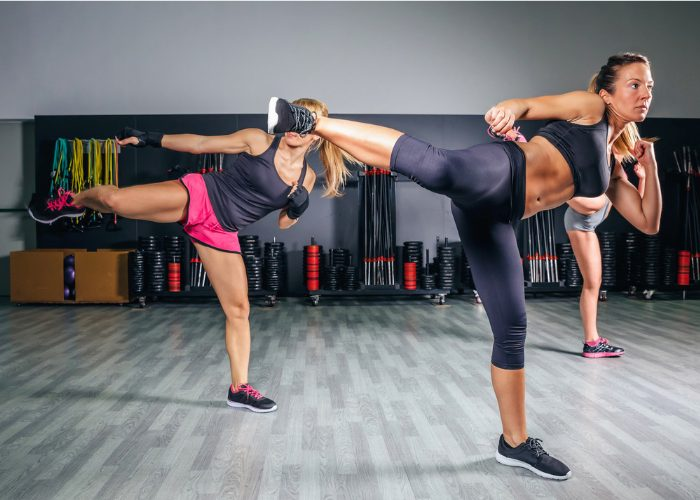 Three women doing side kicks in a kickboxing class