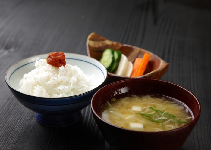 Typical Japanese sides including a bowl of miso soup, a rice topped with an umeboshi, and pickled vegetables