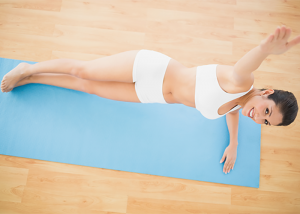 Top down view of woman doing side plank core exercise