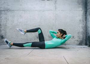 Woman doing bicycle crunch core exercises outdoors