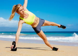 Woman doing side plank core exercise on a kettlebell at the beach