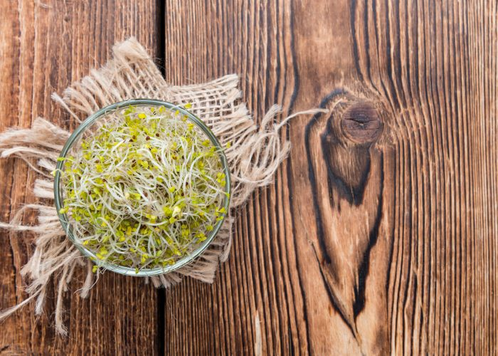 Top down view of broccoli sprouts in a glass bowl on a wooden table