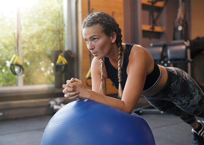 Woman doing plank core exercise on exercise ball