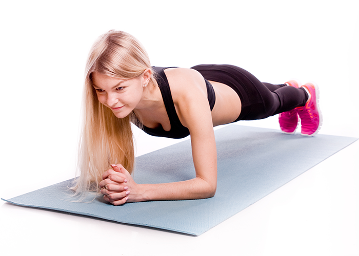 Woman in plank position on a yoga mat