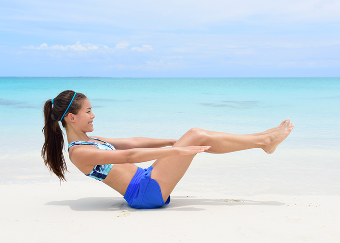 Fit young woman doing the boat core exercise for beginners