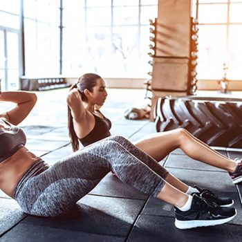 women in a gym doing sit up core exercises