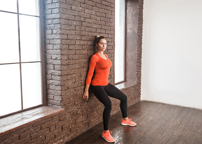 Woman performing wall sit core exercise