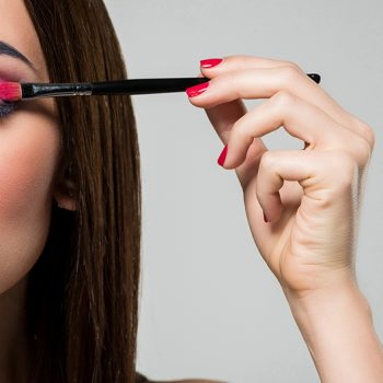 woman with colourful eyeshadow holding up a makeup brush to her eyelid