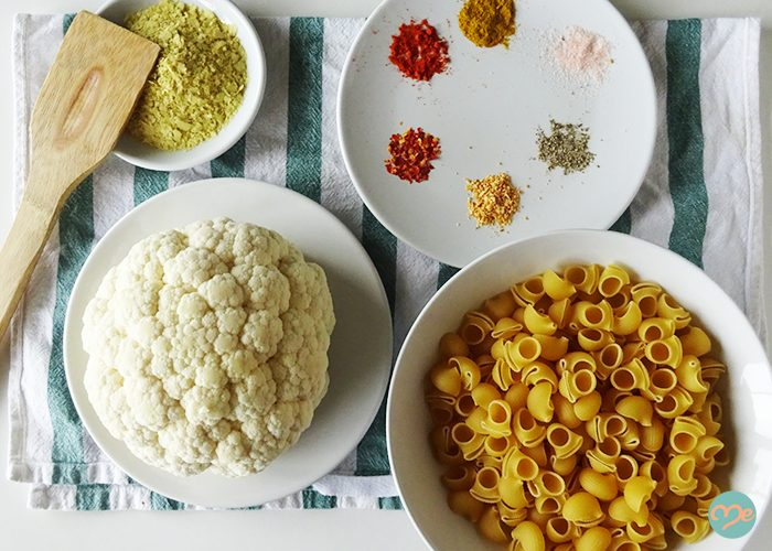 Top down view of dairy-free mac and cheese ingredients such as cauliflower, macaroni, and various spices