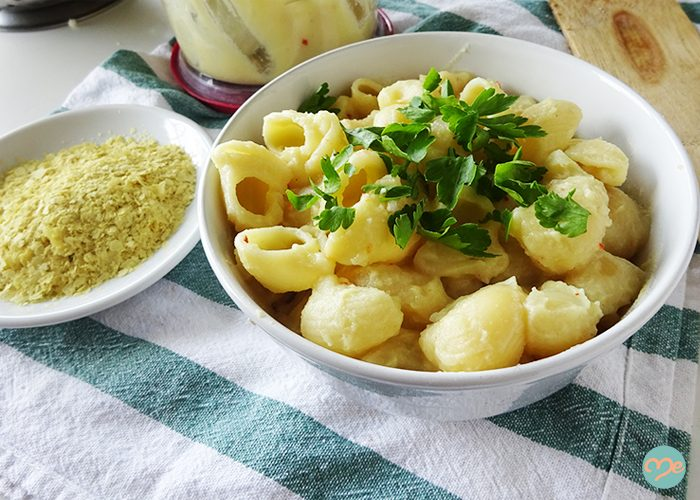 Dairy-free mac and cheese in a white bowl topped with parsley