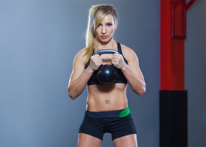 Fit woman at a gym holding a kettlebell in goblet squat starting position