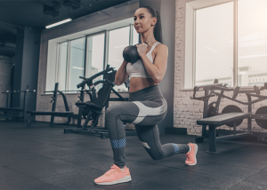 Fit young woman going goblet squat lunges in a gym