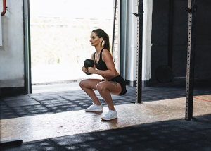 Fit woman in a gym with her knees bent doing a goblet squat
