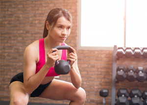 Asian woman doing a goblet squat with knees bent and holding a kettlebell