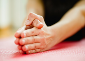 Close up of a woman's hands during a hot yoga class