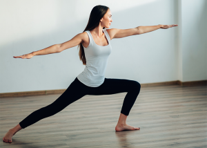 Woman holding warrior pose during hot yoga