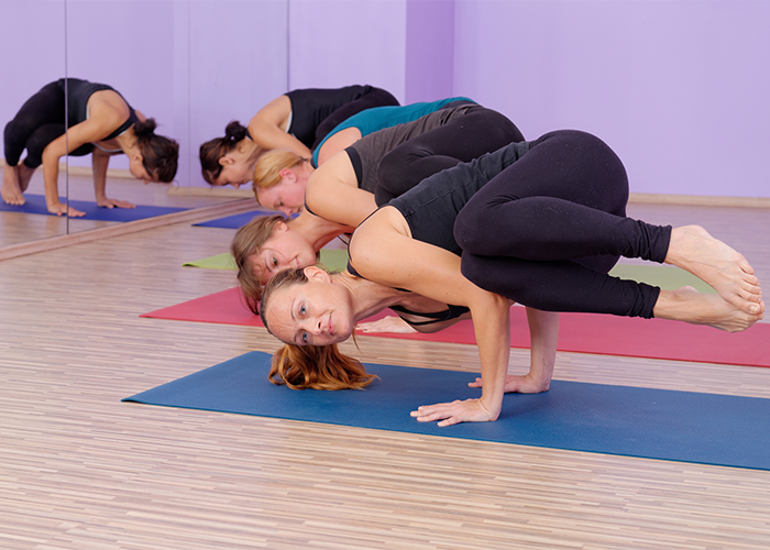 Students performing advanced hot yoga in a hot yoga class