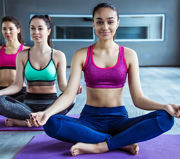 young women sitting in a hot yoga pose