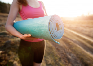 Woman holding a yoga mat with sun shining behind her