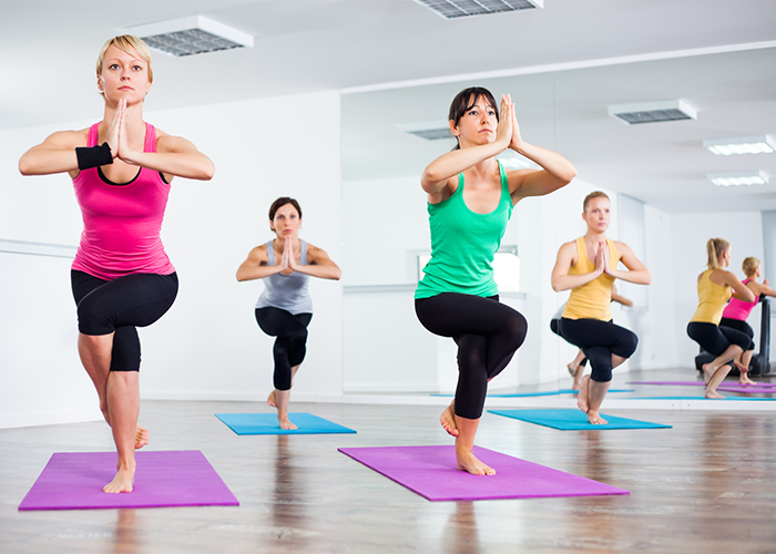 A group of women holding an advanced hot yoga pose in class