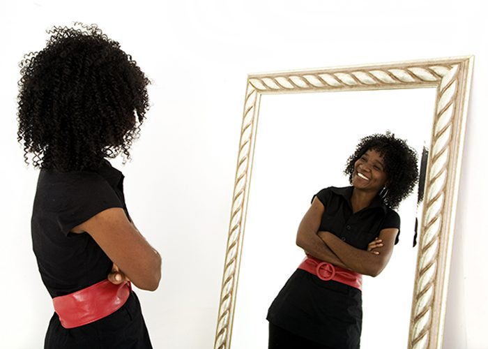 Woman confidently looking at her reflection in the mirror and smiling