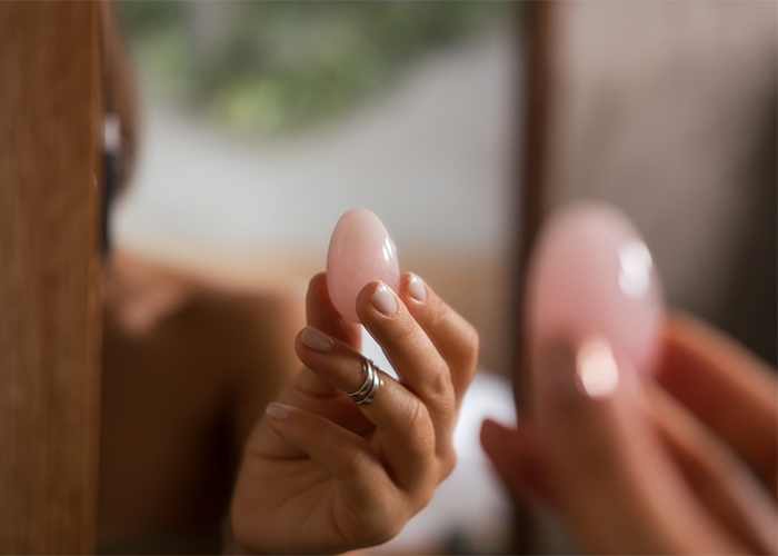 Woman holding up a pink yoni egg to a mirror