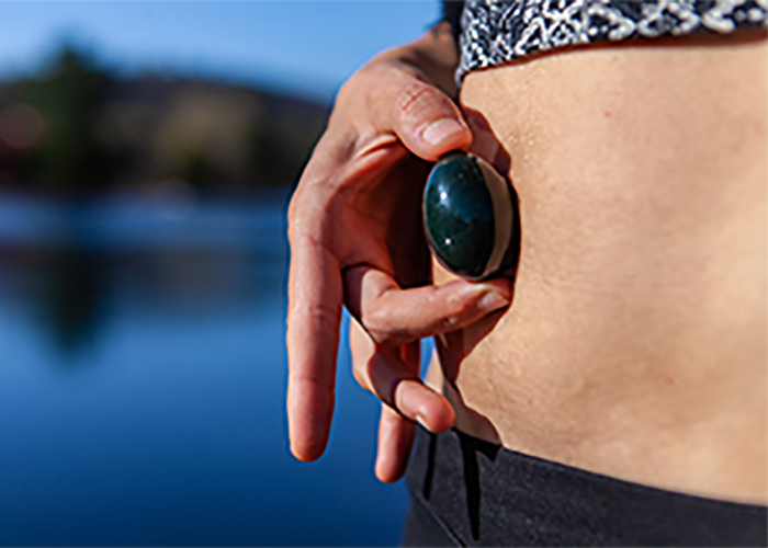 Woman holding a black yoni egg in front of her tummy