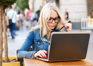 Blonde woman working alone on her laptop at an outdoor desk