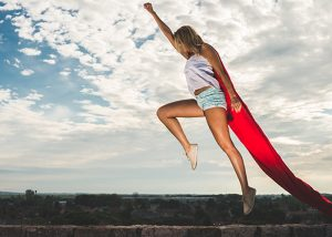 Woman in superwoman pose with a red cape