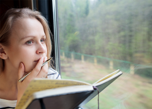 Woman looking pensive with her journal book open on a train