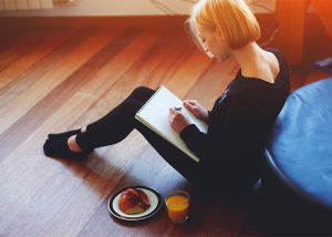 Woman sitting on the floor journaling with breakfast