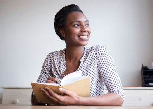 African american woman smiling with an open journal book