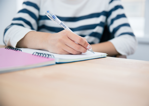Woman in striped shirt writing into her journal