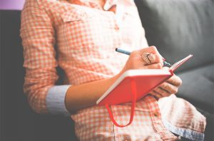 woman with red notebook journaling