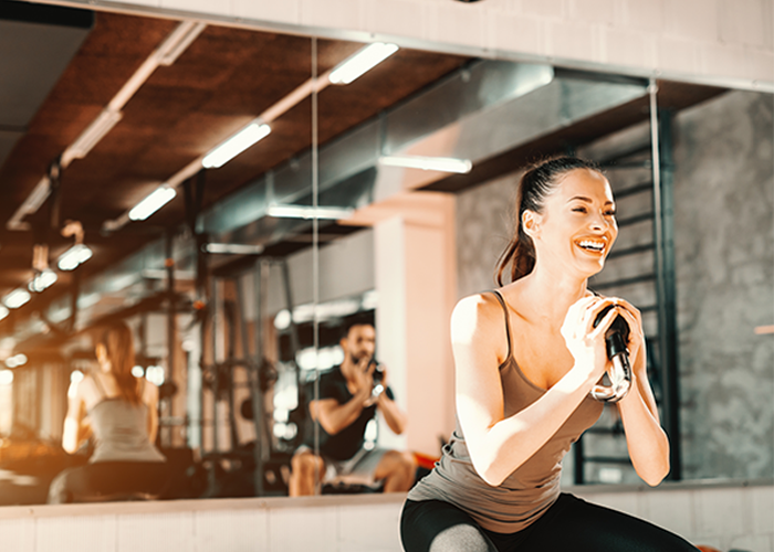 Woman smiling while doing kettlebell goblet squats